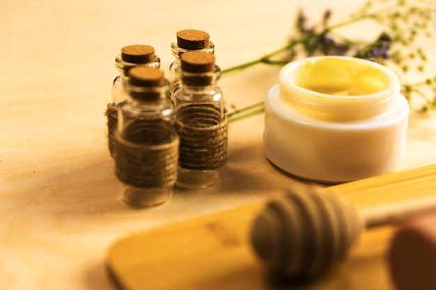 Garrafa de óleo essencial com creme herbal de skincare na mesa