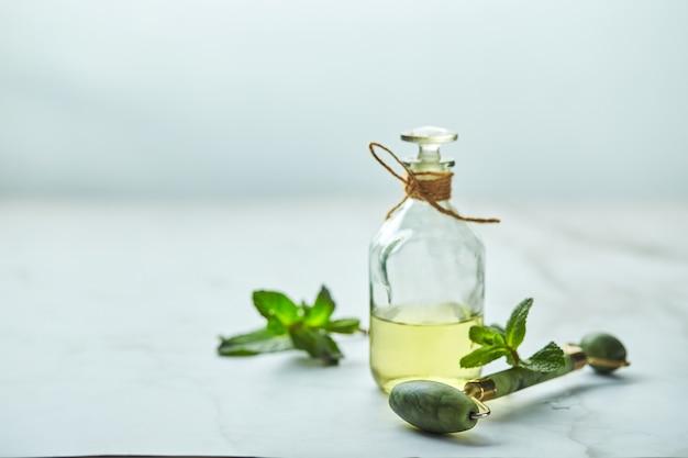 Garrafa de óleo essencial de hortelã e folhas verdes e rolo de massagem jade para o rosto ingredientes orgânicos naturais para cosméticos cuidados com a pele cuidados com o corpo conceito de cuidados de beleza
