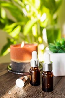 Garrafa de óleos essenciais com vela acesa na mesa de madeira