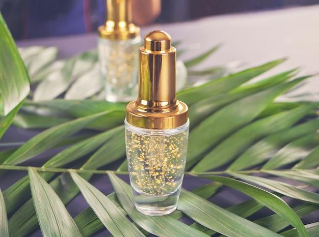 Garrafa de ouro com líquido e folha de palmeira