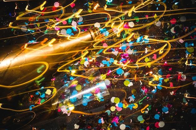 Garrafa de ouro e taça de champanhe em fundo de confete