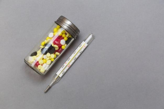 Garrafa de pílulas e termômetro no pano de fundo cinzento