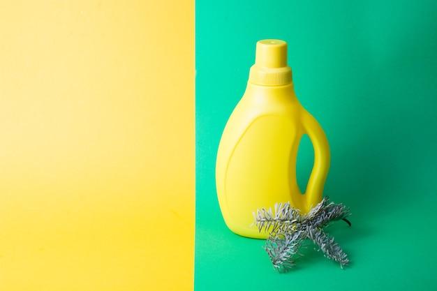 Garrafa de plástico amarela com gel de lavagem e um raminho de abeto em uma superfície verde-amarela