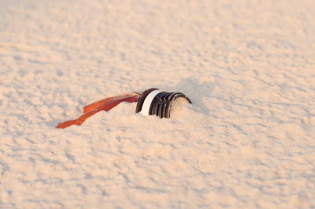 Garrafa de plástico amassada descartada na areia