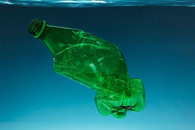 Garrafa de plástico amassada poluindo o oceano