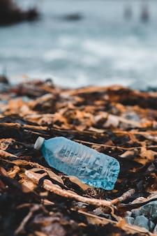 Garrafa de plástico azul nas folhas secas marrons