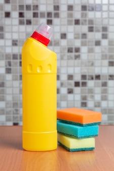 Garrafa de plástico com agente de limpeza e esponjas em cima da mesa
