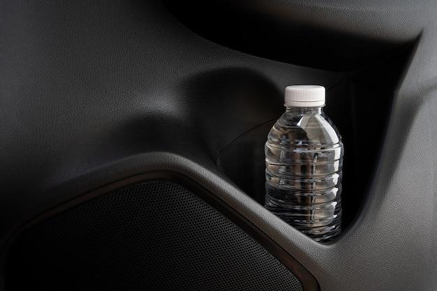 Garrafa de plástico com água deixada no veículo durante o estacionamento no estacionamento ao ar livre, garrafa de plástico com água é causa de incêndio e queima em um carro. evite estacionar em estacionamentos ao ar livre.
