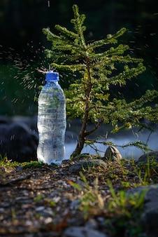 Garrafa de plástico com água potável gelada em desfocar o fundo da pequena árvore e o rio da montanha - água natural pura.