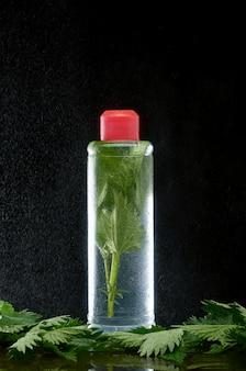 Garrafa de plástico com urtiga fresca em nuvens de pó de água