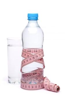 Garrafa de plástico de água potável e fita métrica isolada no fundo branco com traçado de recorte