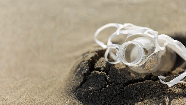 Garrafa de plástico de alto ângulo na areia