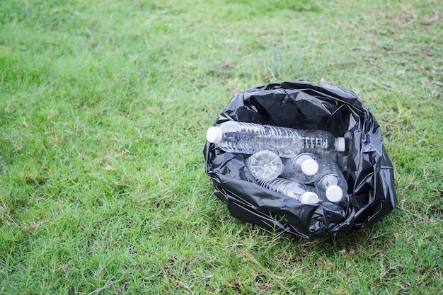 Garrafa de plástico de lixo em saco plástico preto na grama. conservação ambiental do dia da terra concept.copy espaço.