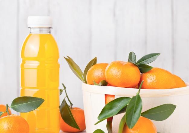 Garrafa de plástico de suco de tangerina mandarim fresco com frutas frescas em caixa de madeira com fundo de madeira clara