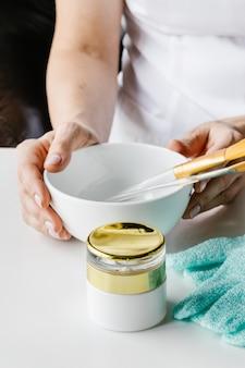 Garrafa de plástico marrom para cosméticos líquidos e tigela de madeira com varas de pedra para massagem facial nas mãos de uma mulher na mesa branca.