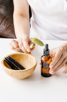 Garrafa de plástico marrom para cosméticos líquidos nas mãos de mulheres, rolo de massagem de jade verde e tigela de madeira com paus de pedra na mesa branca