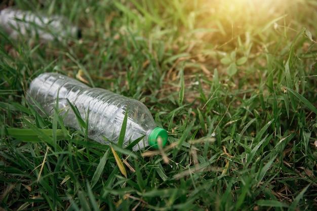 Garrafa de plástico na grama verde. problema de ecologia. poluição ambiental.