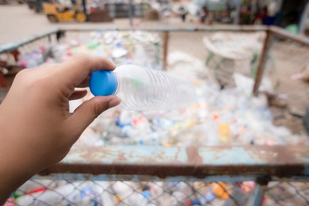 Garrafa de plástico na mão no lixo para reciclar