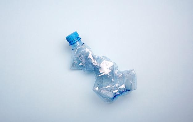 Garrafa de plástico no fundo azul. conceito mínimo de poluição oceânica