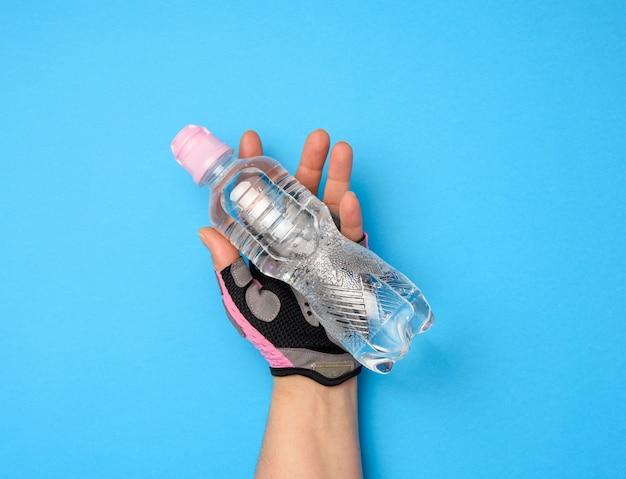 Garrafa de plástico transparente com água doce em uma mão feminina em um fundo azul, close-up