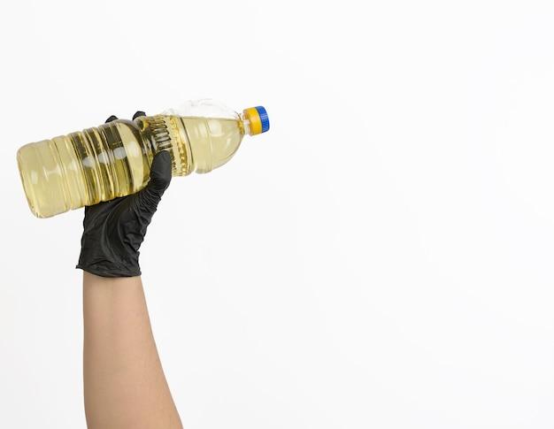 Garrafa de plástico transparente com óleo de girassol na mão
