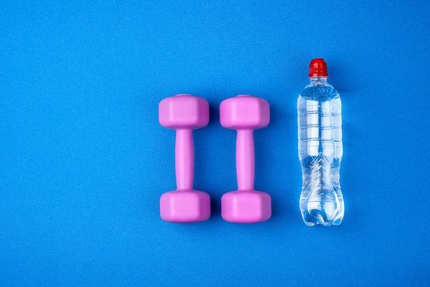 Garrafa de plástico transparente de água e um par de halteres de plástico roxos