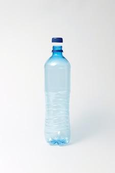 Garrafa de plástico transparente vazia com tampa azul sobre um fundo cinza claro, copie o espaço. .