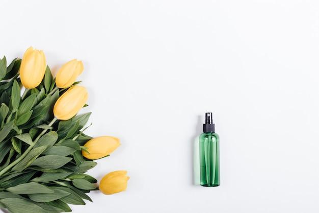Garrafa de plástico verde com água e um buquê de tulipas amarelas sobre fundo branco