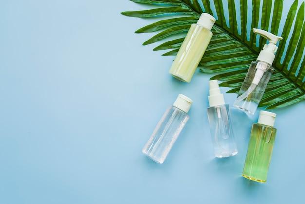 Garrafa de produtos cosméticos à base de plantas na folha verde contra o fundo azul
