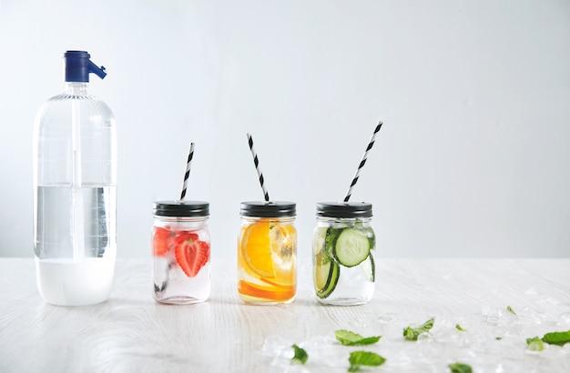 Garrafa de refrigerante perto de três potes rústicos com bebida gelada de morango, laranja, limão, menta, pepino e água com gás