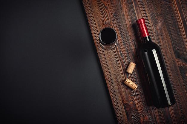 Garrafa de rolhas de vinho e copo de vinho sobre fundo enferrujado
