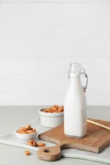 Garrafa de saboroso leite de amêndoa na mesa de madeira colorida