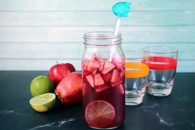 Garrafa de sangria de vinho tinto caseiro com dois copos e frutas na mesa