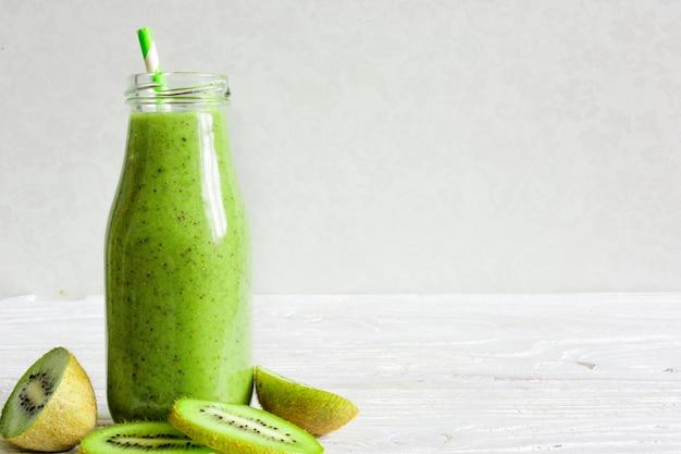 Garrafa de smoothie verde com frutas e bagas frescas de kiwi e banana