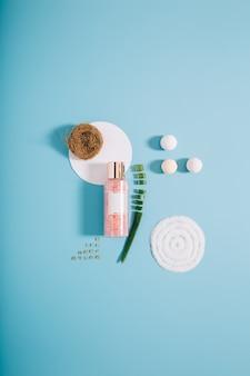 Garrafa de spa de maquete com sal de banho rosa sobre fundo azul. copie o espaço
