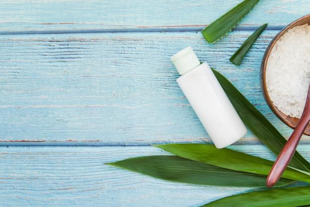 Garrafa de spray; babosa; folhas e sal de rocha no pano de fundo texturizado azul de madeira