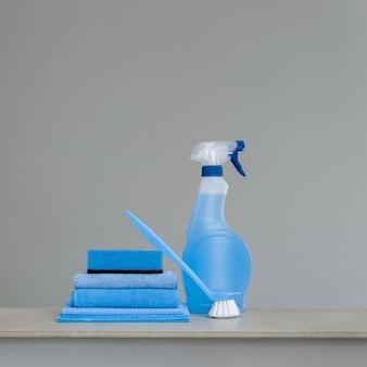 Garrafa de spray de limpeza azul com dispensador de plástico, esponja, esfregando escova para prato e pano para a poeira.