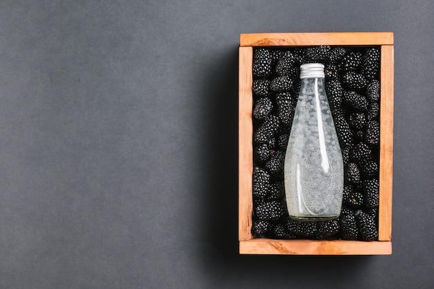 Garrafa de suco de amora na caixa de madeira