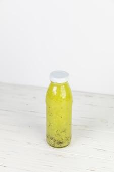 Garrafa de suco de brócolis caseiro fresco na mesa branca