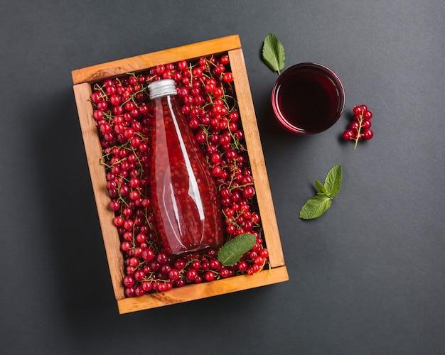Garrafa de suco de cranberry vista superior em caixa de madeira