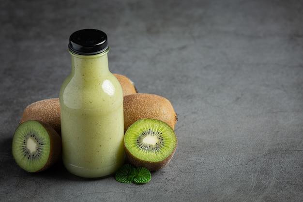 Garrafa de suco de kiwi colocada no chão escuro