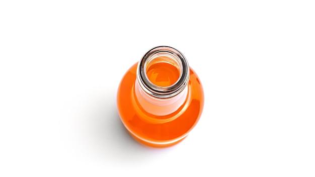 Garrafa de suco de laranja aberta em um fundo branco