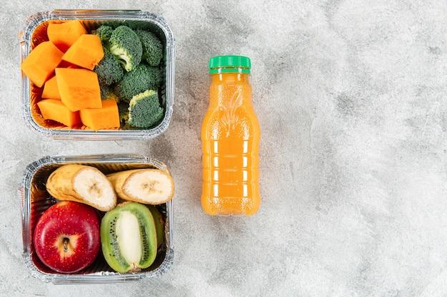 Garrafa de suco de laranja com frutas e legumes em caçarolas