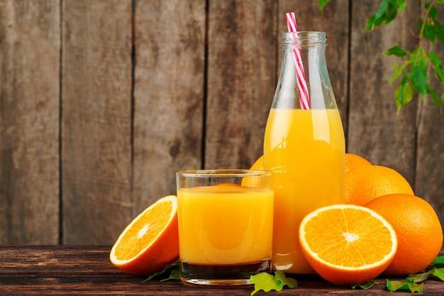 Garrafa de suco de laranja com laranjas na mesa de madeira
