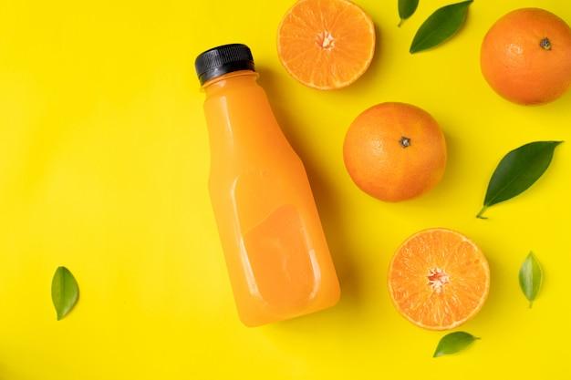 Garrafa de suco de laranja em fundo amarelo.