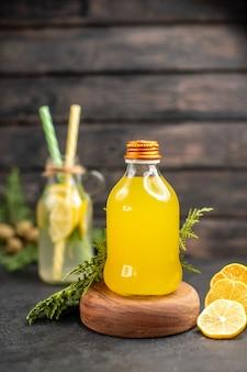 Garrafa de suco de laranja fresco na placa de madeira e limonada de vista frontal