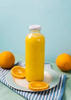 Garrafa de suco e arranjo de laranjas