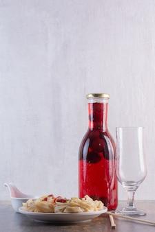 Garrafa de suco vermelho com copo vazio e macarrão na superfície branca