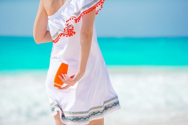 Garrafa de suncream closeup em mãos femininas na praia