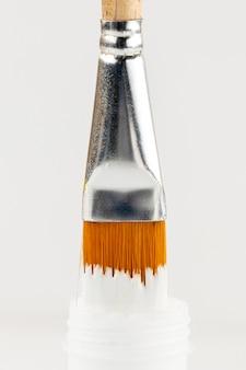 Garrafa de tinta branca e pincel embebido